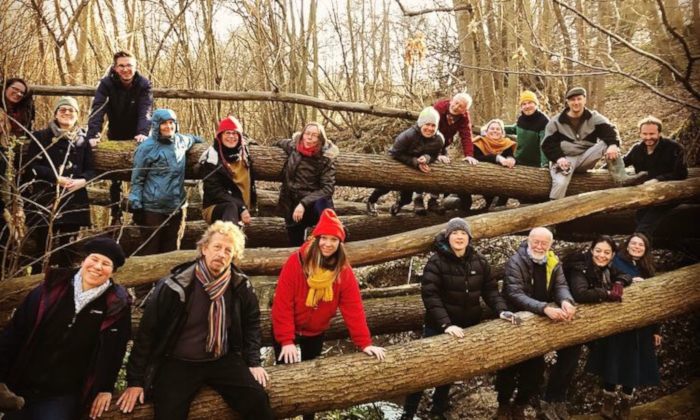 Group shot of the London Sea Shanty Collective on and around a fallen tree